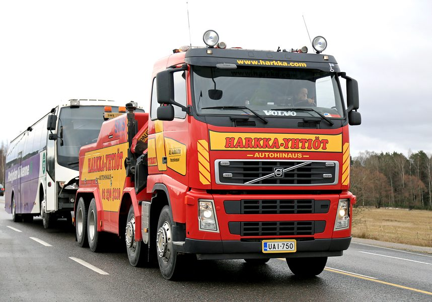 SALO, FINLAND - FEBRUARY 22, 2015: Volvo FH13 heavy duty tow truck tows a coach bus along highway 110. Due to the required skills and equipment, only few Finnish tow companies offer heavy duty towing.